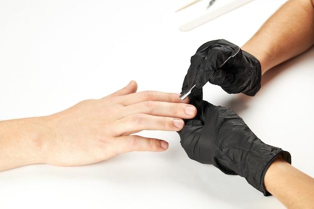 Manicure durante il lavoro utilizzando chiodo in metallo stick. un processo di manicure da uomo. una persona caucasica irriconoscibile che fa servizio di unghie al salone spa.