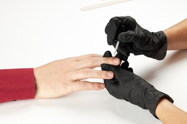 Manicure durante il lavoro utilizzando olio per unghie o smalto. un processo di manicure da uomo. una persona caucasica irriconoscibile che fa servizio di unghie al salone spa.