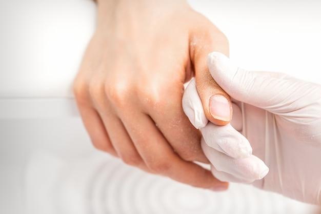 Il manicure tiene il pollice della donna durante una procedura di manicure nel salone del chiodo