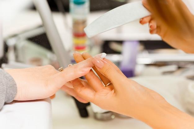 Il manicure fa l'escalation delle unghie. utilizzare la lima per unghie rende la forma delle unghie.
