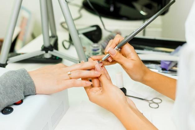 Il manicure fa l'escalation delle unghie.