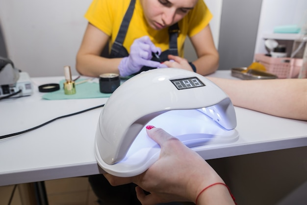 Il maestro manicure sta dipingendo le unghie del cliente in gel gommalacca, un'altra mano si sta asciugando in una lampada uv nel salone di bellezza, le mani si chiudono manicure in guanti sta facendo la manicure.
