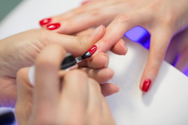 Il maestro del manicure fa il manicure rosso sulla mano della giovane donna. maestro del chiodo della donna che fa le unghie a un cliente della ragazza in un salone di bellezza. prenditi cura delle mani