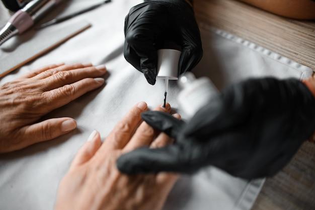 Estetista dipinge le unghie a un cliente anziano, primo piano. salone di bellezza