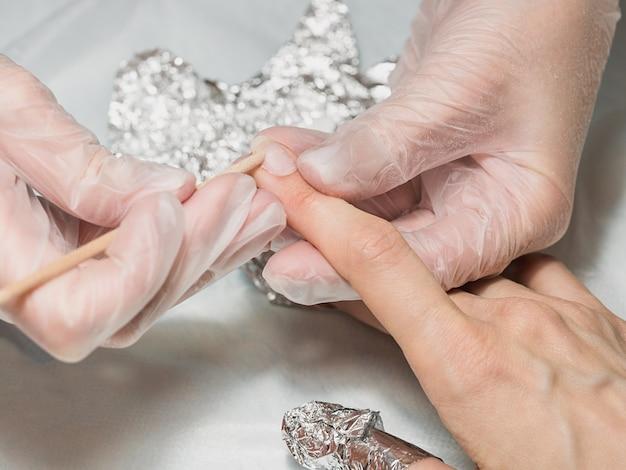 Il manicure rimuove la base dall'unghia con un bastoncino arancione durante la procedura di manicure presso la spa