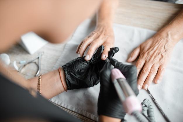 Manicurist tratta le unghie di una donna, primo piano. cura delle unghie. concetto di salone di bellezza