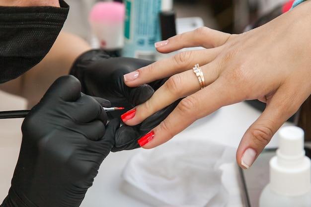 Manicure con guanti neri e maschera nera che fa le unghie di una donna al salone da vicino