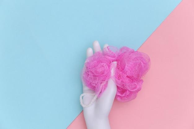 La mano del manichino tiene la spugna da bagno su sfondo pastello blu-rosa. vista dall'alto
