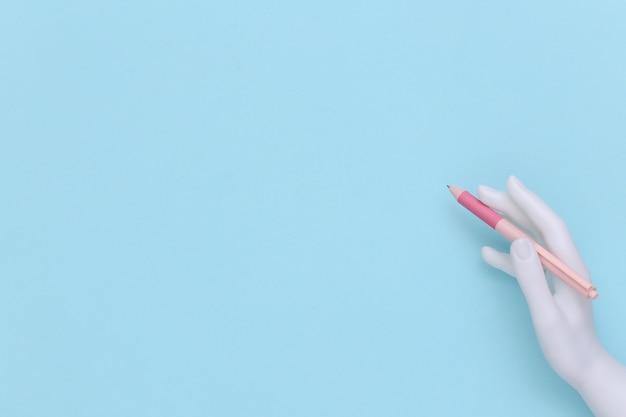 La mano del manichino tiene la penna su fondo blu con lo spazio della copia. vista dall'alto