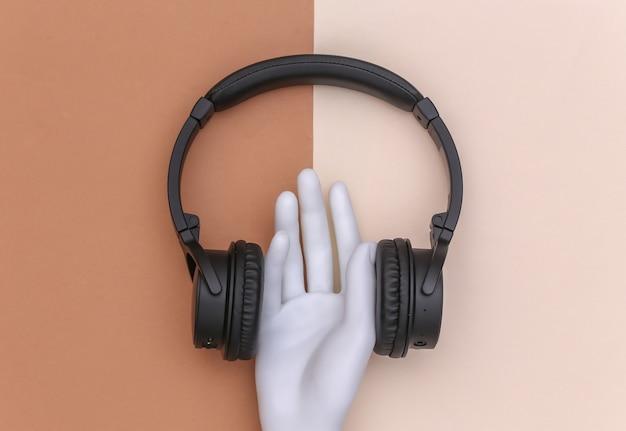 Mano del manichino con le cuffie stereo su fondo beige marrone. arte di concetto di minimalismo. vista dall'alto
