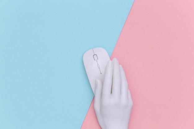 La mano bianca del manichino che tiene il mouse del pc su sfondo rosa pastello blu. vista dall'alto