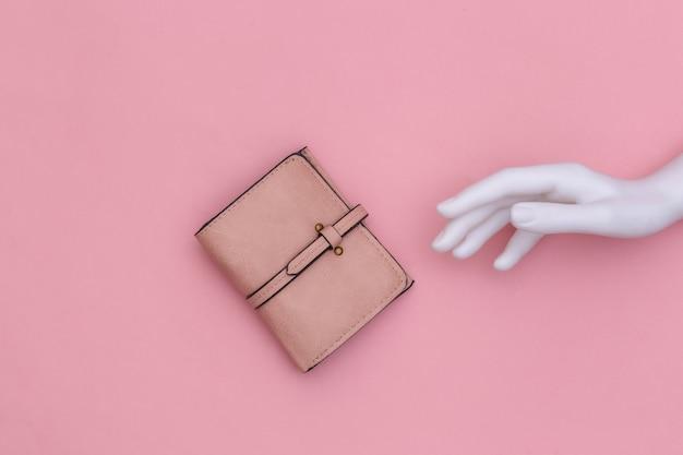 La mano bianca del manichino tocca il portafoglio in pelle su uno sfondo rosa. vista dall'alto