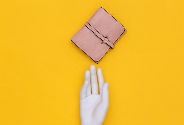 La mano bianca del manichino tocca il portafoglio in pelle su sfondo giallo. vista dall'alto