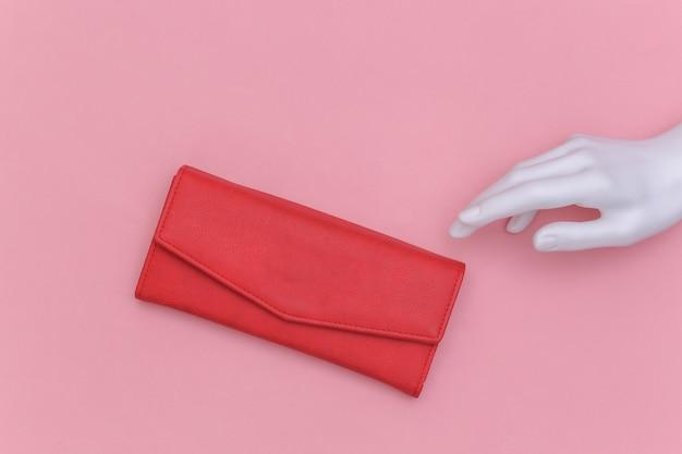 La mano bianca del manichino tocca un portafoglio in pelle rossa su sfondo rosa. vista dall'alto