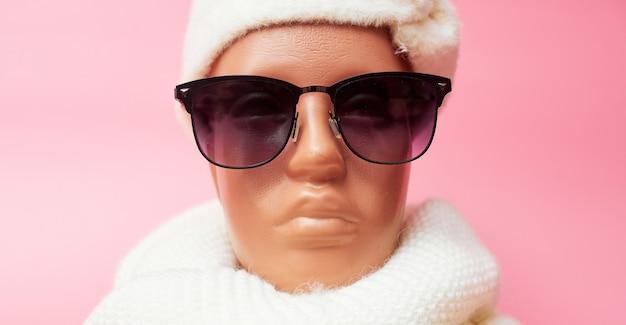 Manichino con occhiali e sciarpa, sconti su abiti e accessori invernali, su fondo rosa