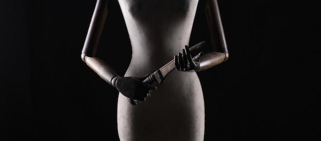 Manichino con coltello su sfondo nero