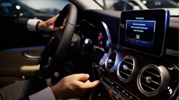 Mans grandi mani su un volante mentre guida un'auto