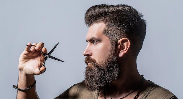Mans taglio di capelli nel negozio di barbiere. forbici da barbiere, negozio di barbiere. forbici da barbiere.