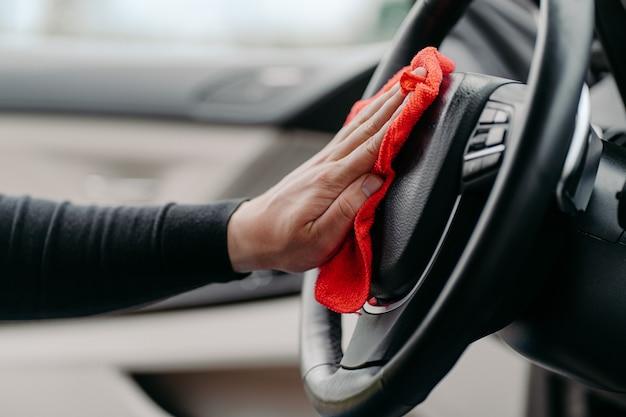 Equipaggia la pulizia degli interni di auto di lusso a mano. pulire il volante durante il coronavirus. lavaggio auto dall'interno. concetto di igiene
