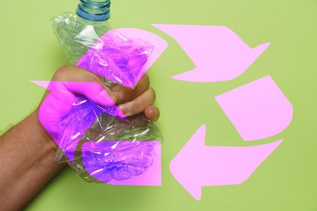 Man mano che schiaccia una bottiglia di plastica con il simbolo di riciclaggio rosa concetto di riciclaggio senza plastica
