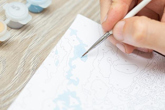 La mano di un uomo tiene un pennello e disegna un'immagine in base ai numeri. disegno su tela. barattoli di vernice numerati. hobby creativo. pittura per principianti primo piano, messa a fuoco selettiva.