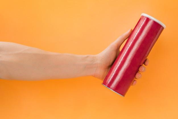La mano dell'uomo tiene un tubo vuoto rosso da patatine su uno sfondo arancione patate fritte mockup mock up