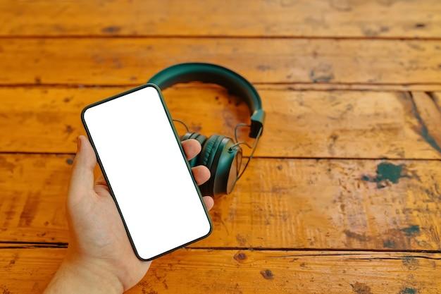 La mano dell'uomo tiene lo smartphone con lo schermo di visualizzazione dello spazio di copia vuoto su cuffie wireless nere ...