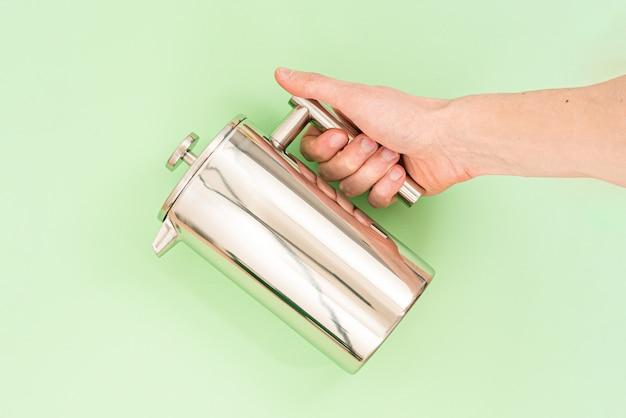 La mano dell'uomo tiene la stampa francese in acciaio inossidabile su uno sfondo verde chiaro Foto Premium