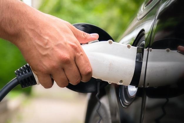 Equipaggia la mano inserendo la spina del caricatore nell'auto elettrica in un ambiente verde