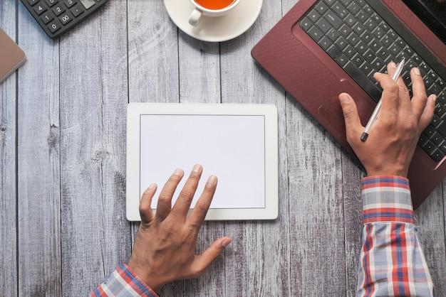 Equipaggia la mano lavorando sulla tavoletta digitale sulla scrivania in ufficio