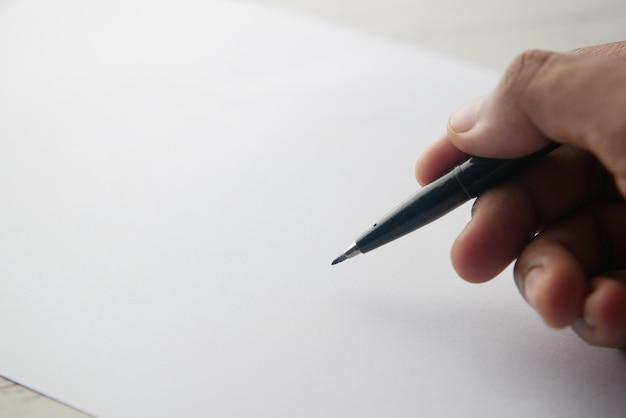 Man mano che scrive con la penna su carta