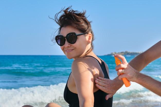 Equipaggia le mani che applicano la crema di protezione solare alla pelle matura della donna, spazio della spiaggia del mare