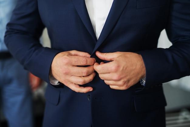 Equipaggia le mani che mettono un bottone sul bellissimo gilet.