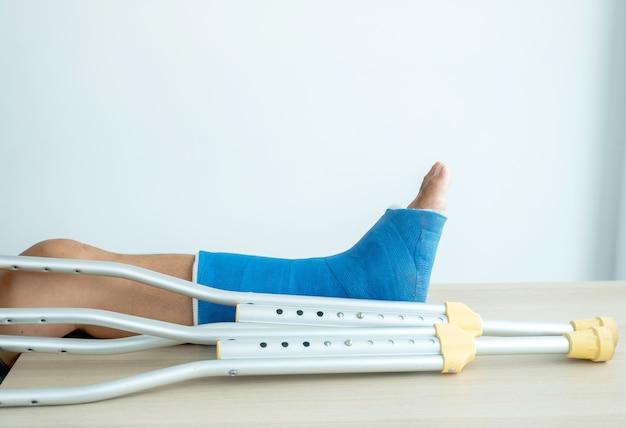 La gamba dell'uomo usa le stampelle per camminare dopo un intervento chirurgico di recupero con le ossa rotte