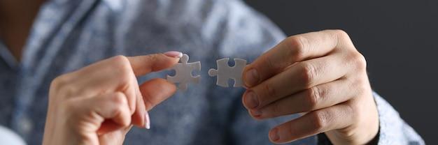 Equipaggia e la mano di una donna che collega un primo piano di due pezzi di puzzle. risoluzione del concetto di conflitti familiari