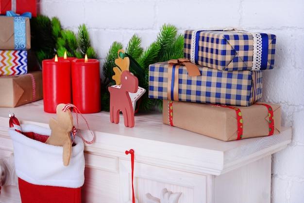 Mensola del camino con regali e decorazioni natalizie sulla superficie del muro di mattoni