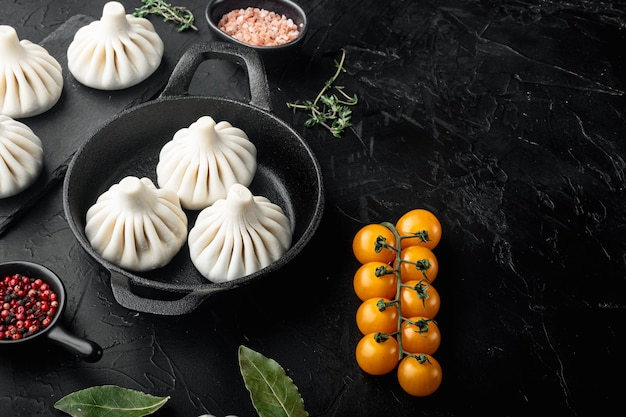 Manti o gnocchi di manty, popolare set di piatti asiatici, in padella in ghisa, su pietra nera