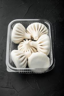 Gnocchi manti o manty, popolare servizio di piatti asiatici, in vassoio di plastica, su pietra nera