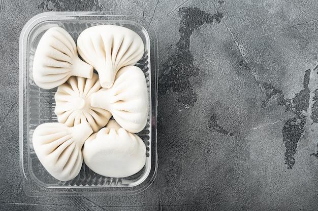 Gnocchi manti o manty, popolare servizio di piatti asiatici, in vassoio di plastica, su pietra grigia