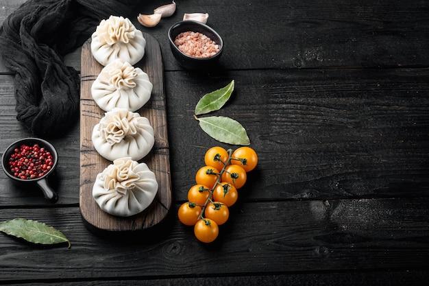 Manti, set di ravioli tradizionali turchi, sul tavolo di legno nero