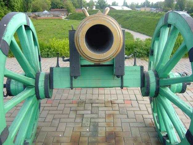 Il mantello di un vecchio cannone su ruote puntato su un telaio in piedi su un piedistallo di pietra