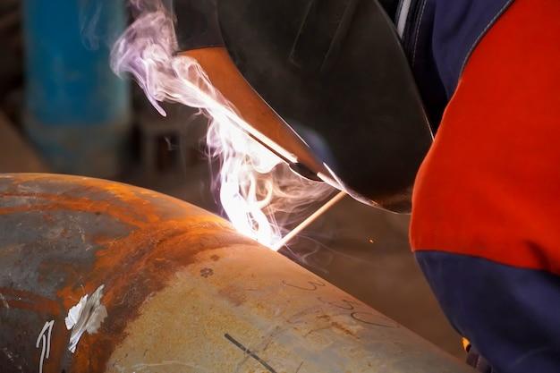 Saldatura ad arco manuale. un saldatore effettua le riparazioni a un cordone di saldatura difettoso di una conduttura per petrolio, benzina e gas dopo prove non distruttive