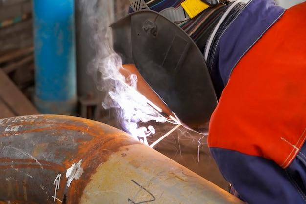 Saldatura ad arco manuale. un saldatore fa una saldatura su una conduttura per petrolio, benzina e gas