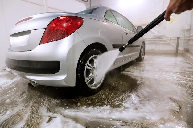 Autolavaggio manuale. lavaggio veicolo di lusso con pompa dell'acqua ad alta pressione. self service di pulizia dell'auto. lavare la schiuma con acqua dall'auto. lavoratore uomo lava la macchina.