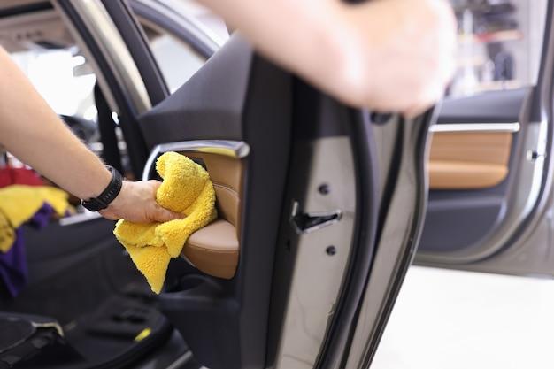 Pulizia manuale del pannello della portiera interna dell'auto con il concetto di servizi di lavaggio auto in panno in microfibra