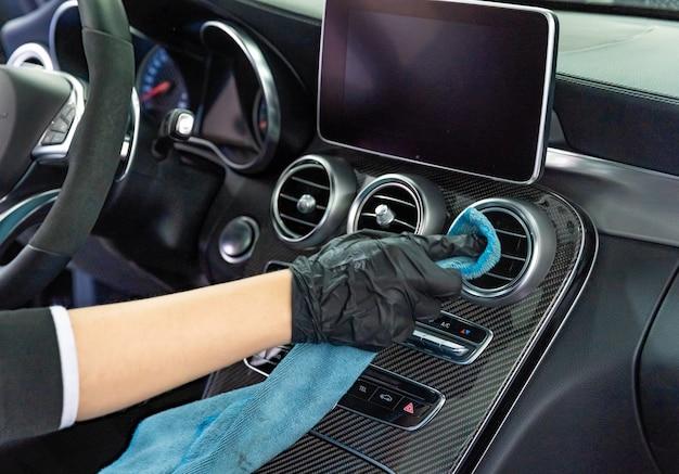 Pulizia manuale degli interni delle auto di lusso con un panno in microfibra