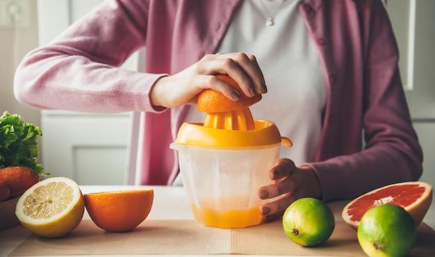 Procedura di spremitura manuale e produzione di succo di frutta a casa dall'arancia Foto Premium