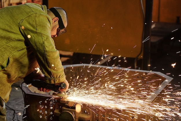 Operaio in abbigliamento da lavoro protettivo che lavora con saldatura dell'acciaio nell'officina di assemblaggio