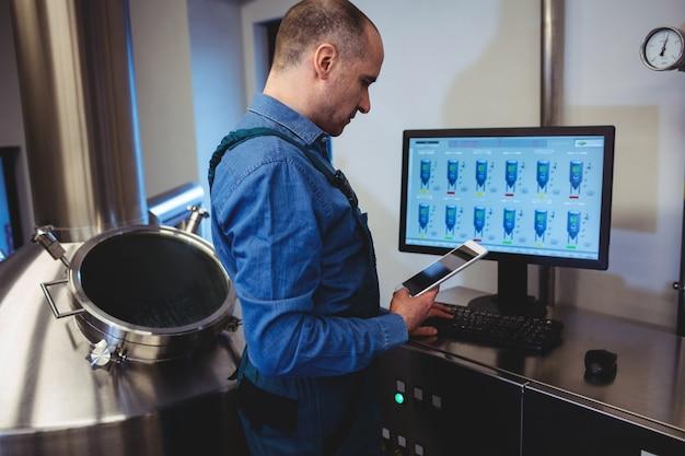Produttore che tiene compressa digitale mentre si lavora al computer