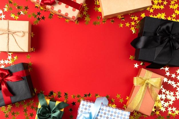 Molti bei regali con fiocchi per eventi importanti su uno sfondo stellato rosso con posto per il testo